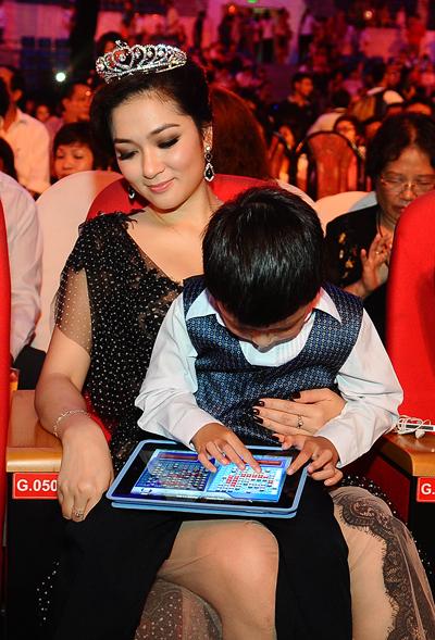Khi Jennifer tất bận thay đồ và chuẩn bị cho giờ lên sóng, Bảo Nam ngoan ngoãn ngồi bên Hoa hậu Nguyễn Thị Huyền và chơi game.