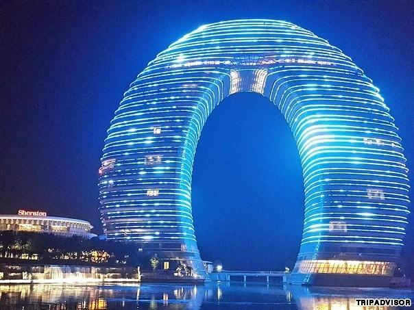 3. Sheraton Huzhou Hot Spring, Huzhou, Trung Quốc. Nổi tiếng với thiết kế hình chiếc bánh donut, khu nghỉ dưỡng Sheraton Huzhou Hot Spring, Trung Quốc sở hữu những tiện ích và dịch vụ vô cùng khác lạ, đặc biệt. Ví như cầu dưới nước làm đường nối giữa hai tòa tháp. Ban đêm, đèn sẽ chiếu sáng toàn bộ tòa nhà, sáng rực rỡ lung linh.